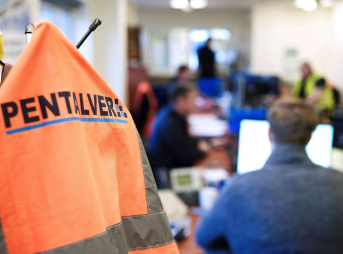 Pentalver branded orange jacket hanging in office